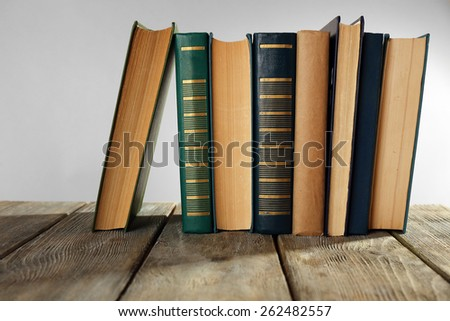 Old books on wooden table on gray background - stock photo