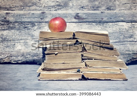 Old books. Pile of old books and one red apple on a wooden background, close up - stock photo