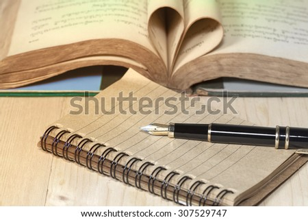 old books, pocket clock, paper and fountain pen on wooden 