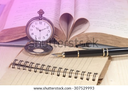 old books, pocket clock, paper and fountain pen on wooden ,