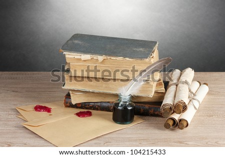 old books, scrolls, feather pen and inkwell on wooden table on grey background - stock photo