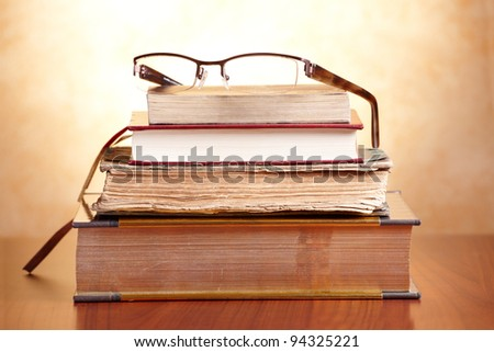 Old books with glasses on the wooden table - stock photo