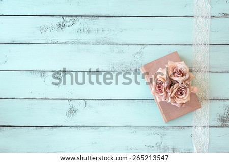 Old books with lace, rose and keys on shabby chic mint background, top view point - stock photo