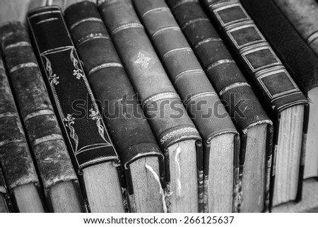 Old books with leather covers lay on the shelf, vintage stylized monochrome photo - stock photo