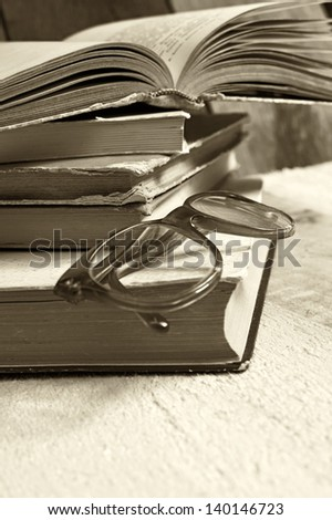 Old books with reading glasses. Selective focus on glasses. - stock photo