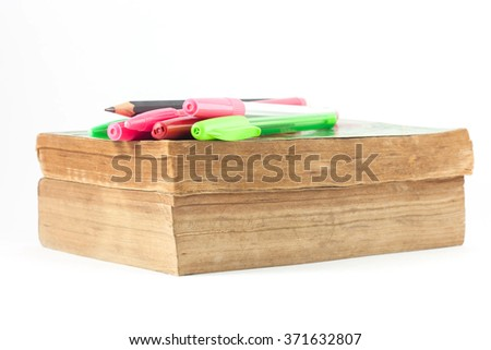 Old books with some pens on white background, selective focus. - stock photo