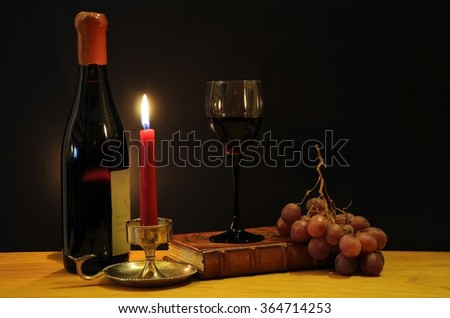 Old bottle of esteemed italian wine with glass, candle and grapes - stock photo