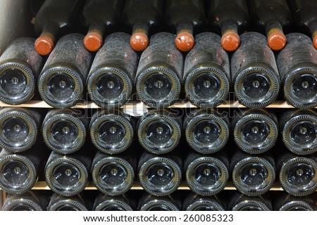 Old bottles of wine in rows in wine cellar - stock photo