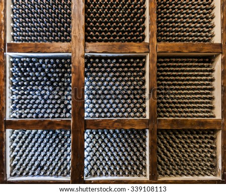 Old bottles of wine maturing in a wine cellar vault - stock photo