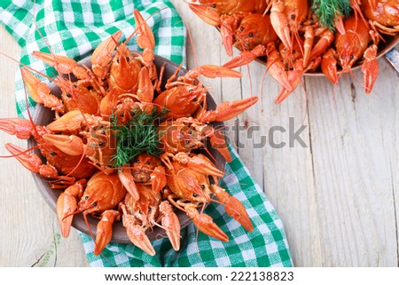Old bowl with red boiled crawfish on a wooden table in rustic style, close-up, selective focus on some crawfishes - stock photo