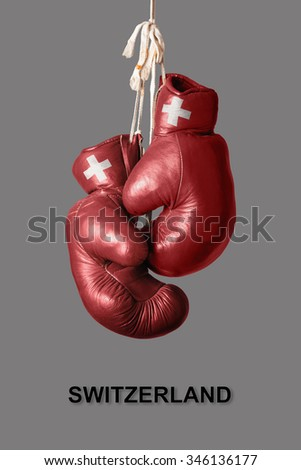 old Boxing Gloves in the Color of Switzerland - stock photo