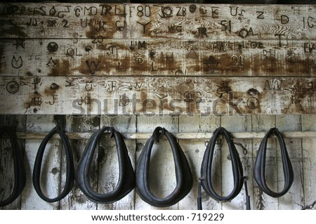 Old branding iron marks, burned onto the wall of a horse stable. - stock photo