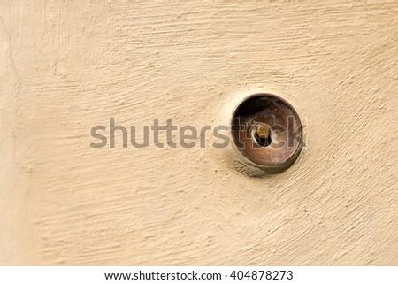 Old brass doorbell button on a beige wall in Portovenere or Porto Venere (UNESCO world heritage site) - La Spezia, Liguria, Italy - stock photo