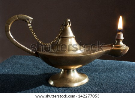 old brass magic lamp burning on the table - stock photo