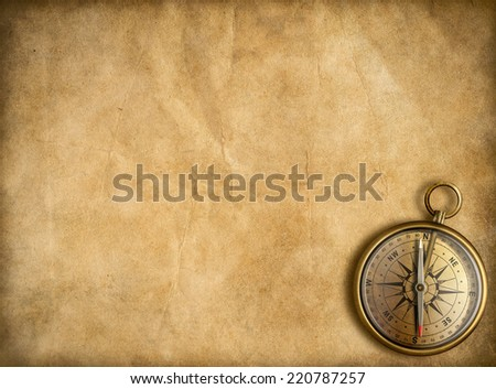 old brass or golden compass with vintage map background - stock photo