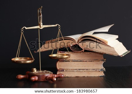 Old brass weight scale near books on black background - stock photo