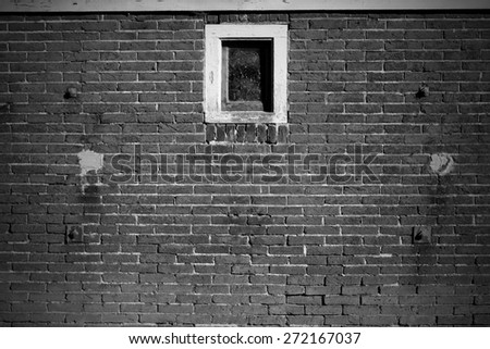 Old brick wall background with a windows in black and white. - stock photo