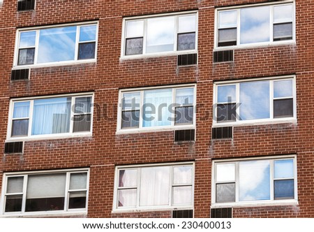 old brick wall buliding. cloudy sky reflected in window's glass - stock photo