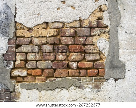 Old brick wall exposed under decaying stucco in Charleston, South Carolina - stock photo