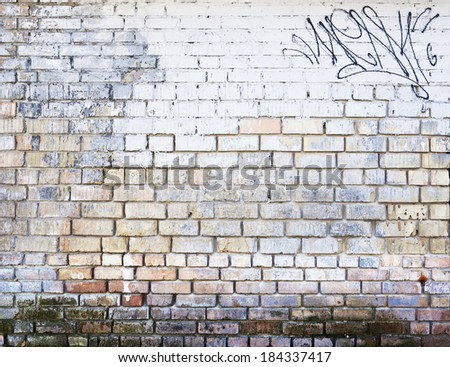 old brick wall painted in bluish white with a graffiti - stock photo