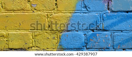 Old brick wall painted yellow and blue colors. - stock photo