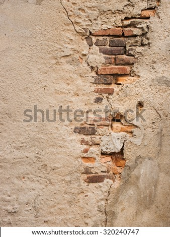 Old brick wall with cracked stucco layer. - stock photo