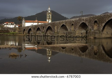 Old bridge and reflection (medieval city Ponte de Lima in the North of Portugal), just before heavy rain - stock photo