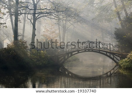 Old bridge in misty autumn park - stock photo