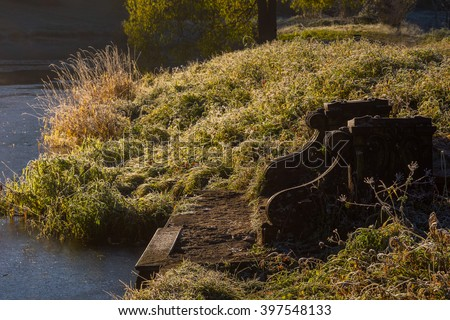 Old broken bench on sunset in park was create of Pavlovsk Park located in Saint-Petersburg Russia shortly before sunset. Bench beside river. - stock photo