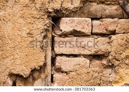 Old broken brick and dirt wall  - stock photo