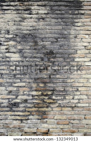 Old broken brick wall, detail of a textured background brick wall in a town - stock photo
