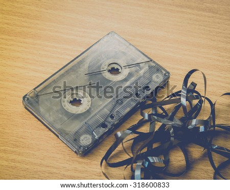 Old broken cassette isolated on wood in vintage tone - stock photo