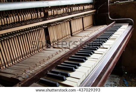 Old broken disused piano with damaged keys - stock photo