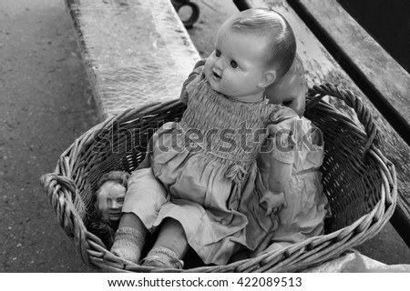Old broken dolls at flea market. Child abuse concept. Black and white photo. - stock photo