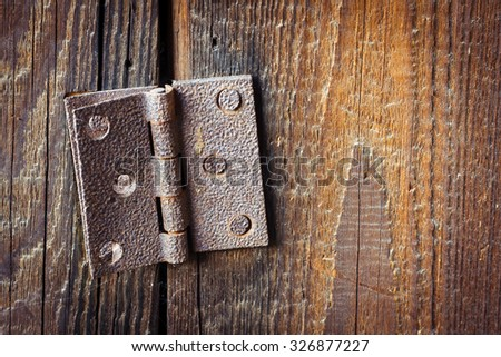 Old broken rusty hinge with bolts in it over a wooden background - stock photo