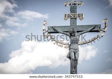Old bronze baroque cross with the crucifix on the Charles' bridge in Prague, Jesus Christ on the cross. Artistic desaturated vintage edit with a vignette. - stock photo