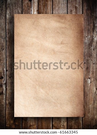 Old brown paper on wood panel - stock photo
