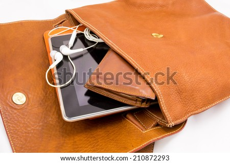 Old Brown Shoulder bag with wallet and modern portable audio earphones. - stock photo