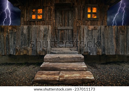 Old brown wooden hut with glowing windows, fence and big wooden stairs, dark stormy sky with lightnings - stock photo