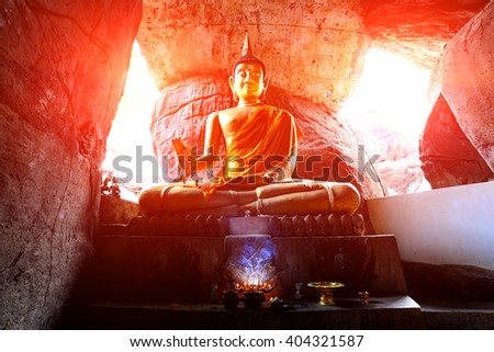Old Buddha statue in cave - stock photo