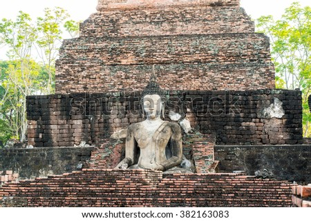 Old buddha with old brick pagoda in the temple at Sukhothai Historical Park in Sukhothai Province, Thailand - stock photo