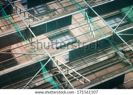 Old building facade under construction with green protective mesh - stock photo