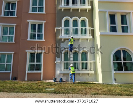 Old building is being re-painted and repaired by workers. - stock photo