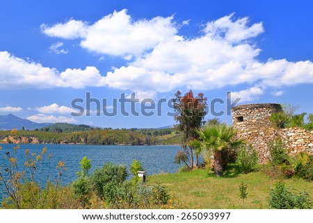 Old building n sunny banks of the Marathon lake, Greece - stock photo