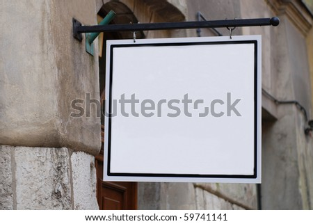 old building, white sign henging on a wall - stock photo