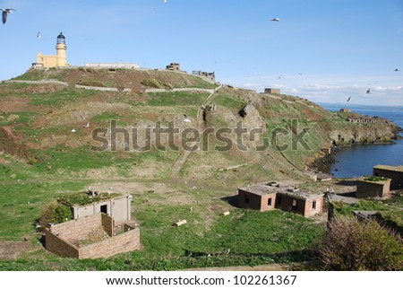 Old Buildings and Lighthouse - stock photo