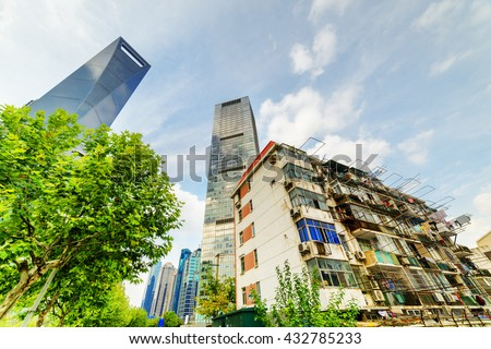 Old buildings coexist with modern skyscrapers in the Pudong New District (Lujiazui) of Shanghai, China. The Shanghai World Financial Center (SWFC) is visible at left on blue sky background. - stock photo