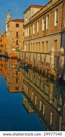 Old buildings in waters of Venice canal - stock photo