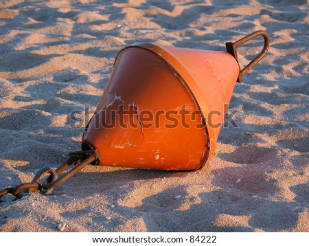 Old buoy in the sand - stock photo