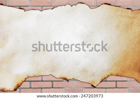 old burned paper on the brick wall background - stock photo